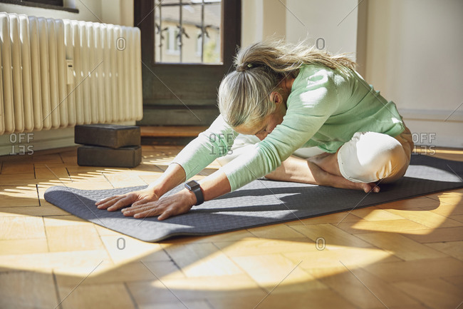 Woman exercising on exercise mat over floor in living room