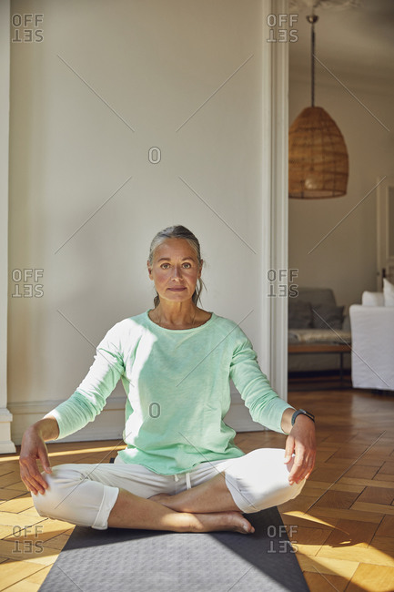 Woman sitting on exercise mat against wall at home