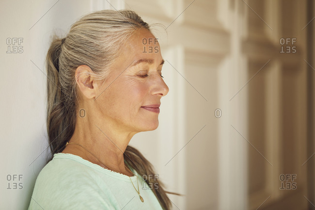 Wrinkled woman with eyes closed by door at home