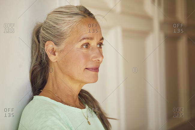 Wrinkled woman looking away by door at home
