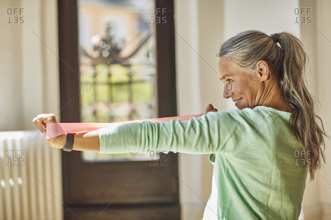 Smiling woman exercising with resistance band in living room