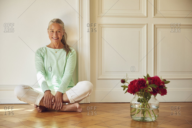 Confident woman sitting on floor by flower vase at home