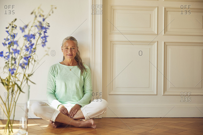 Confident woman sitting on floor against wall at home