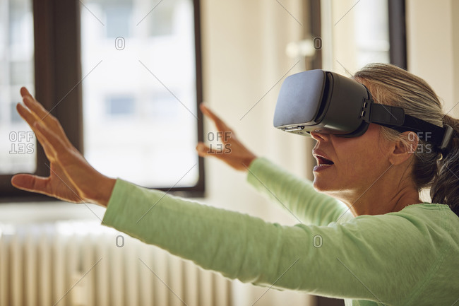 Woman using VR glasses at home