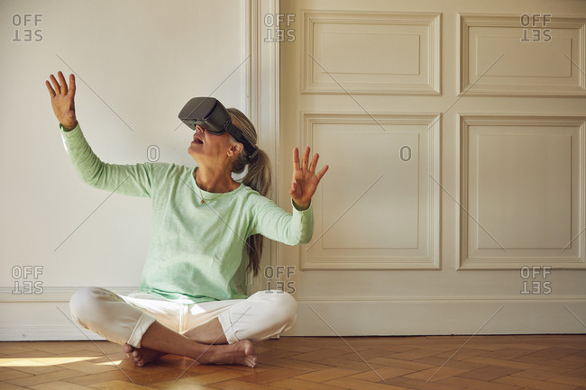 Woman using VR glasses while sitting on hardwood floor at home