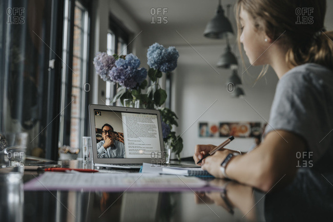 Teenage girl studying from home- using laptop