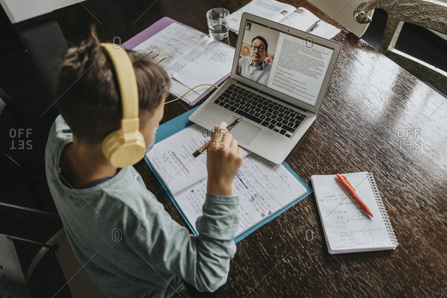 Schoolboy learning at home- using laptop and headphones