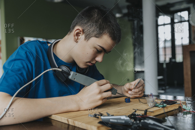 Boy sitting at home using soldering iron