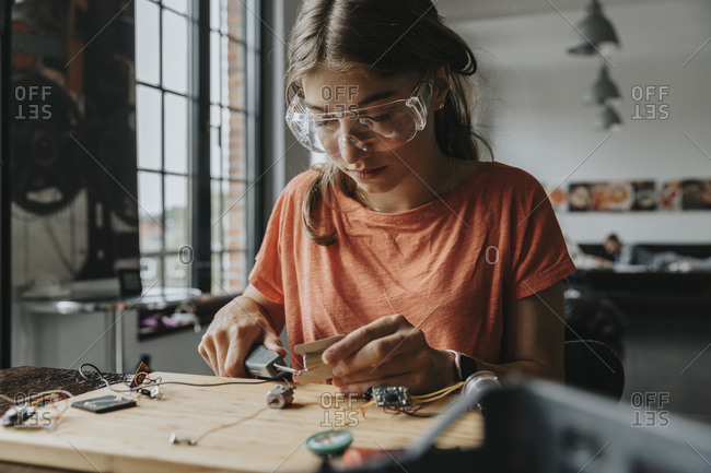 teenage girl tinkering with soldering iron at home
