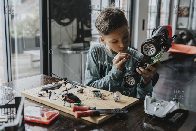 Boy assembling on remote-controlled toy car with screwdriver