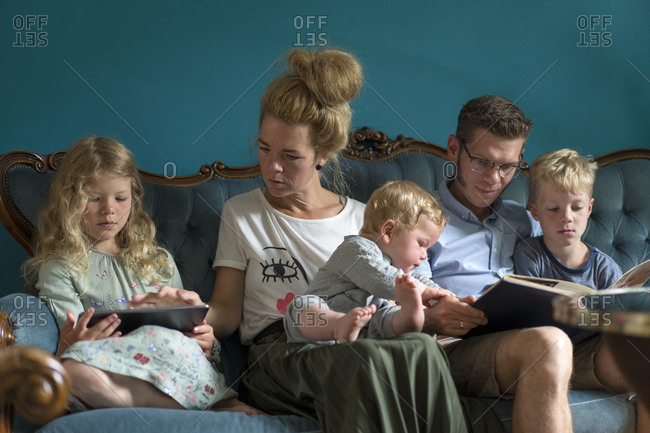 Family sitting on sofa with digital tablet and photo album in living room at home