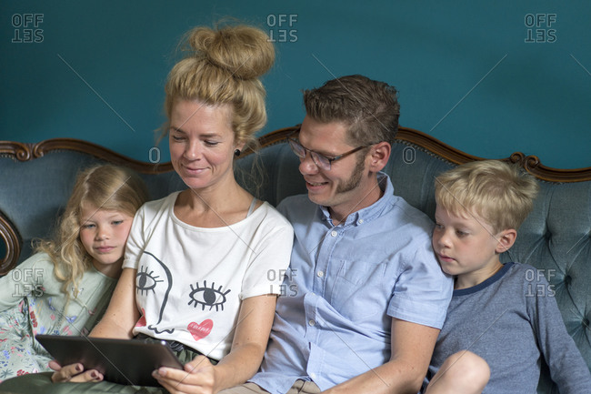 Family sharing digital tablet while sitting on sofa in living room at home