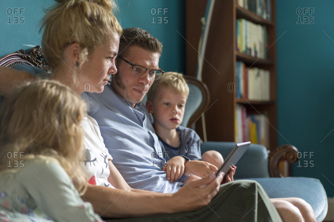 Family with digital tablet sitting on sofa in living room at home