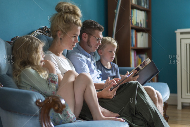 Family sitting with digital tablet and photo album on sofa in living room at home