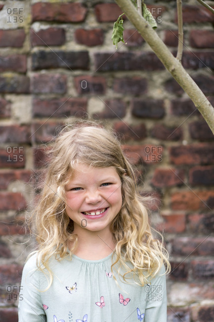 Cheerful blond girl standing against brick wall at back yard
