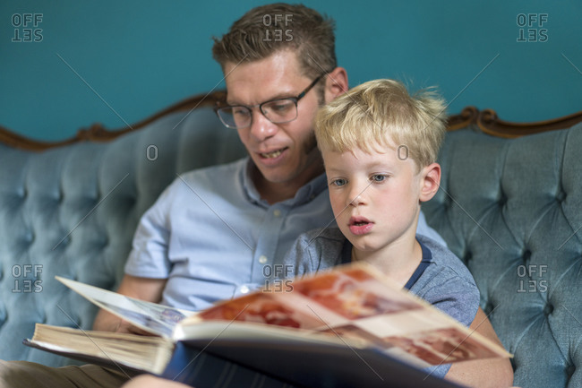 Cute blond boy looking at photo album with father while sitting on sofa in living room