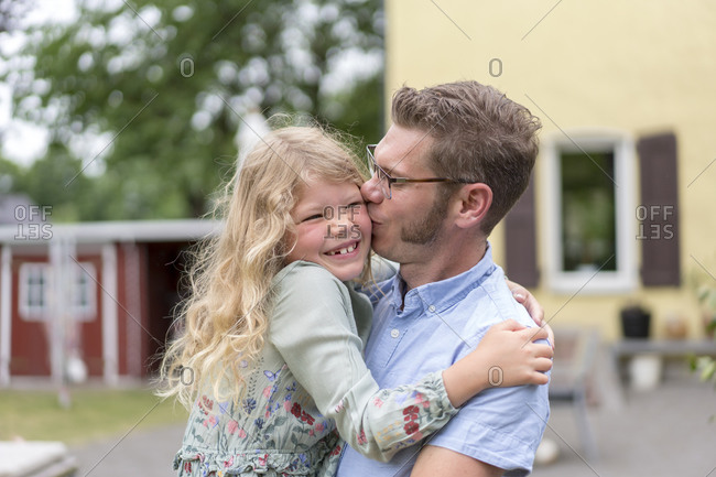 Man kissing happy blond daughter while carrying her at back yard