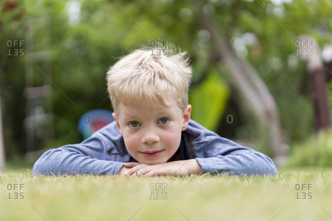 Cute blond boy lying on grass at back yard