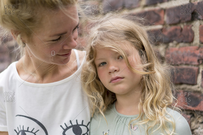 Blond girl with mother against brick wall at back yard