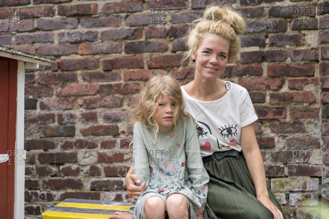 Smiling woman with daughter with blond hair sitting against brick wall at back yard
