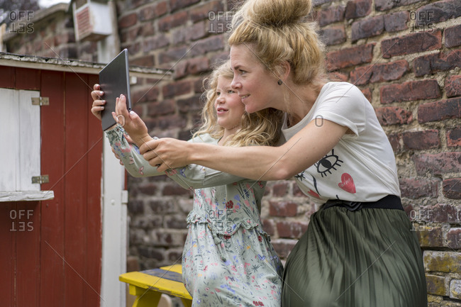 Smiling girl taking selfie with mother through digital tablet against brick wall at back yard