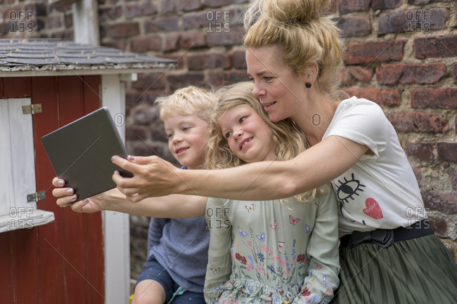 Woman taking selfie with kids through digital tablet against brick wall at back yard