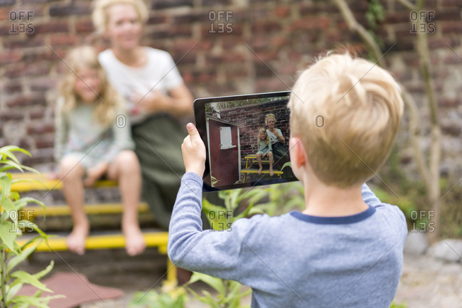 Boy photographing mother and sister through digital tablet against brick wall at back yard