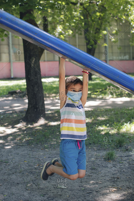 Boy wearing face mask while hanging in playground during COVID-19