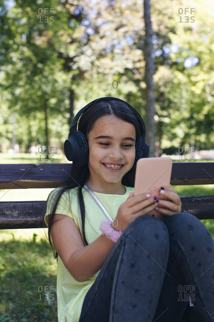 Smiling girl using smart phone while sitting on bench in park