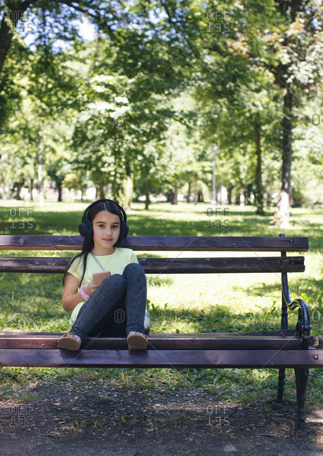 Cute girl with headphone sitting on bench in park