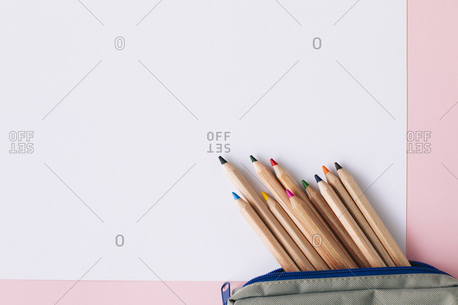 Colored pencils in pouch on blank white paper over pink background