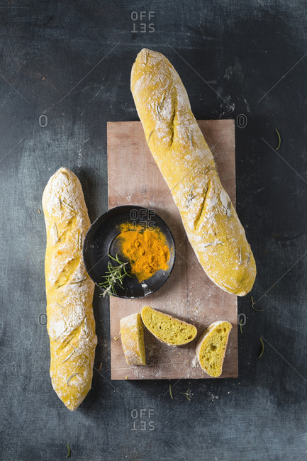 Cutting board- fresh baguettes and bowl with turmeric and rosemary