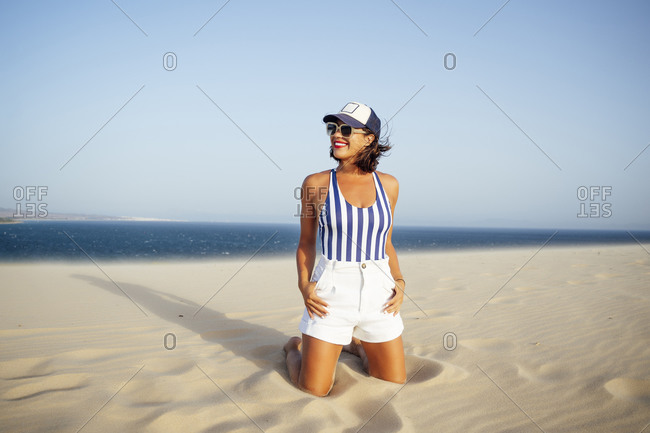 Smiling woman kneeling on sand while looking away at beach against clear blue sky