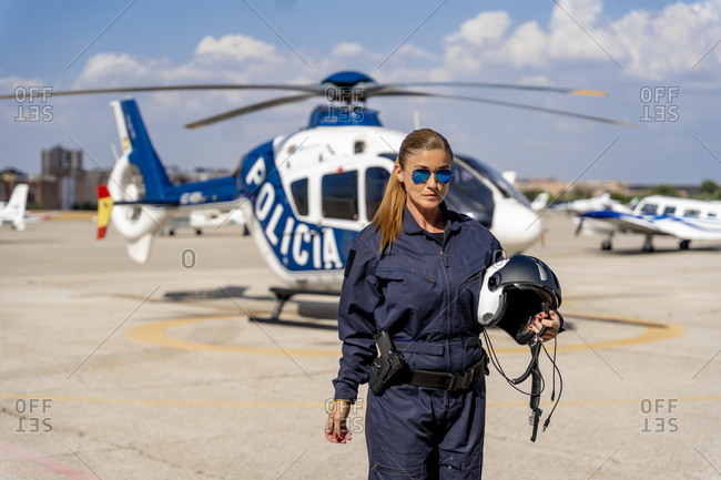 Confident female police pilot holding helmet while standing at helipad