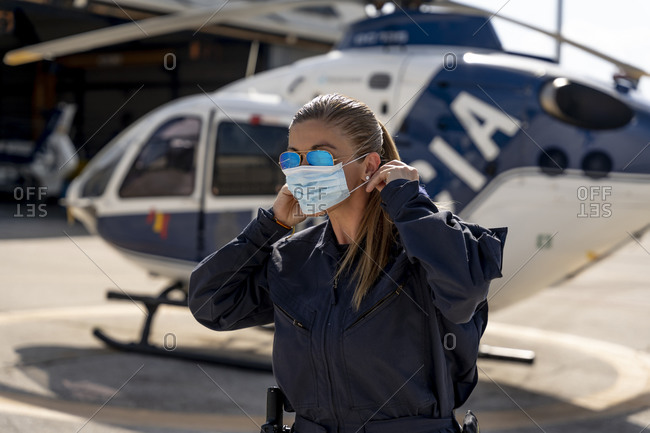 Female police pilot wearing protective face mask during coronavirus outbreak