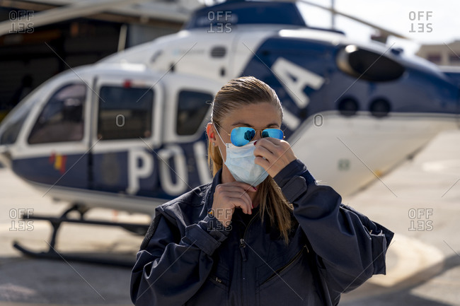 Female police pilot wearing protective face mask
