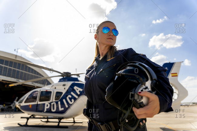 Confident female police pilot standing against sky on sunny day