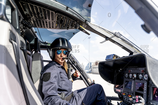Female police pilot wearing sunglasses in helicopter