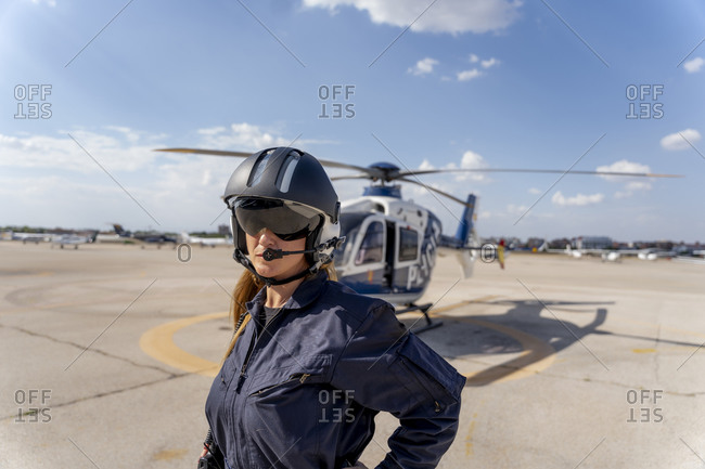 Female police pilot wearing helmet while standing at helipad
