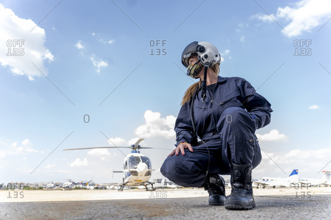 Female police pilot crouching at helipad against sky