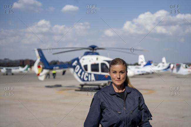 Confident female police pilot in uniform at helipad