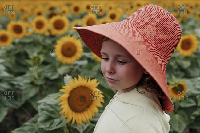 Cute girl wearing sun hat in sunflower field during summer