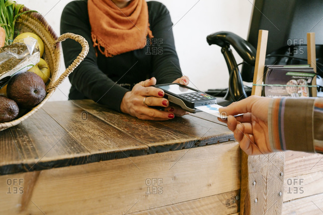 Female cashier assisting customer in payment through credit card at checkout in store