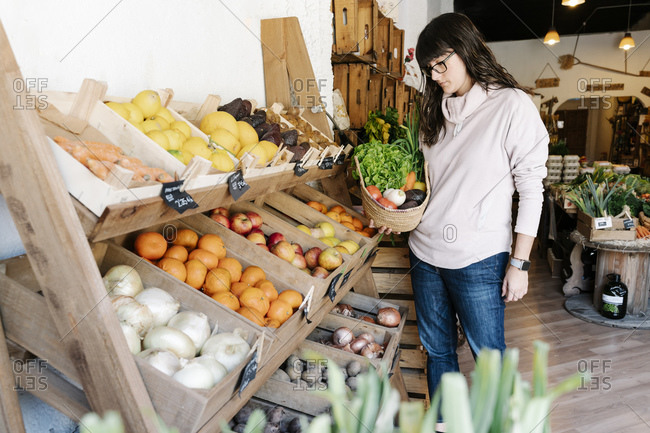 Female customer picking vegetables in basket from grocery store