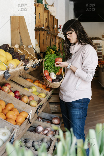 Woman shopping in store while holding basket and looking at apple