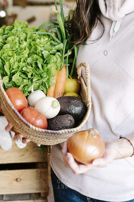 Close-up of vegetable basket held by female customer at store