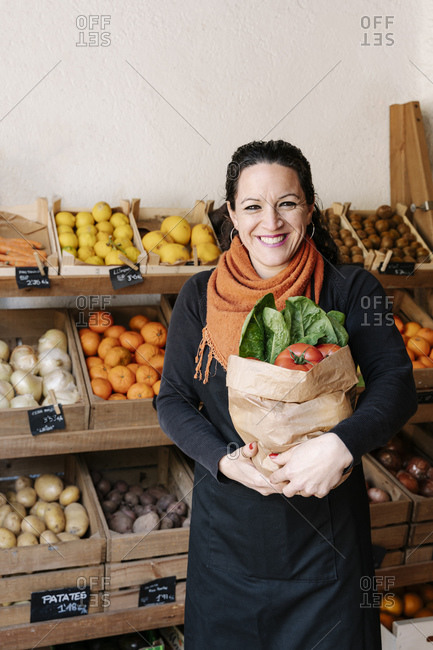 Cheerful saleswoman holding bag of vegetables standing against boxes at store