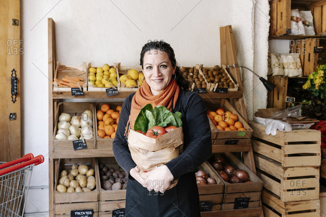 Smiling saleswoman holding vegetable bag at store