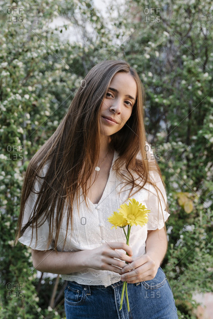 Young woman holding yellow flowers in springtime