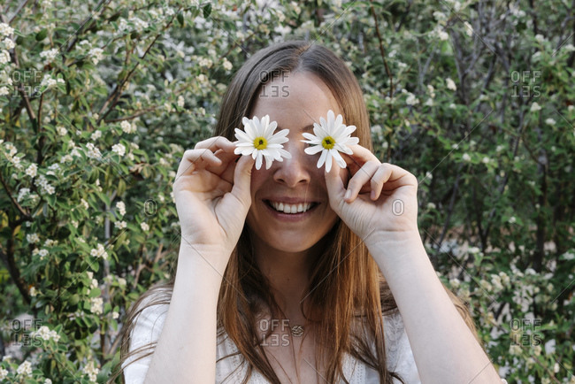 Smiling woman covering eyes with white flowers against plants in park during spring